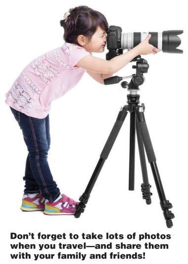 Girl photographer looking behind a camera adjusting lens.